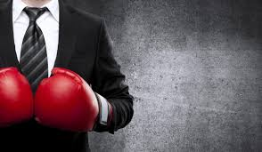 Guy in a suit wearing boxing gloves