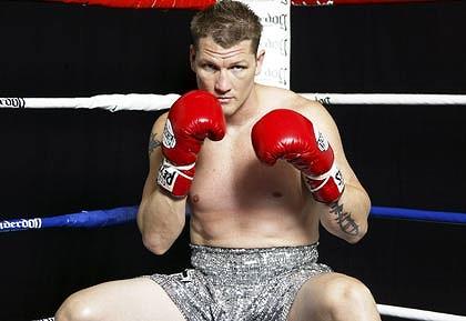Man in boxing corner on stool wearing gloves