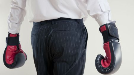 Guy shirt and suit pants wearing boxing gloves