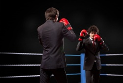 Two competitors wearing suits in ring with boxing gloves