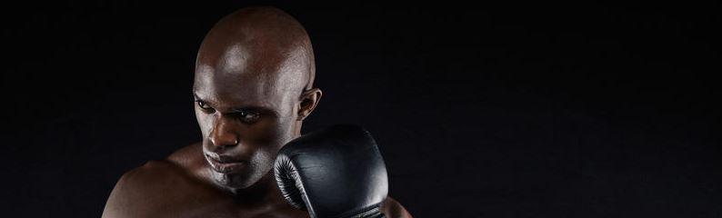 Bald Black man wearing a boxing glove