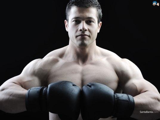 Muscular guy wearing boxing gloves